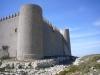 Castell de Montgrí – Torroella de Montgrí - En primer pla veiem les restes d'una pedrera, que al mateix temps va servir per envoltar l'edificació d'un petit fossat