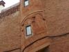 Colònia Güell - Element adossat a la façana lateral de la casa del carrer Aranyó, núm. 23, que resol originalment el problema de la pèrdua d'espai interior que origina la necessitat d'una escala d'unió entre pisos. És una escala de caragol que imita una torreta, amb elements decoratius imitant arquets cecs i el coronament en forma de ràfec. L'element es destaca netament de la paret per la col·locació inversa dels maons.